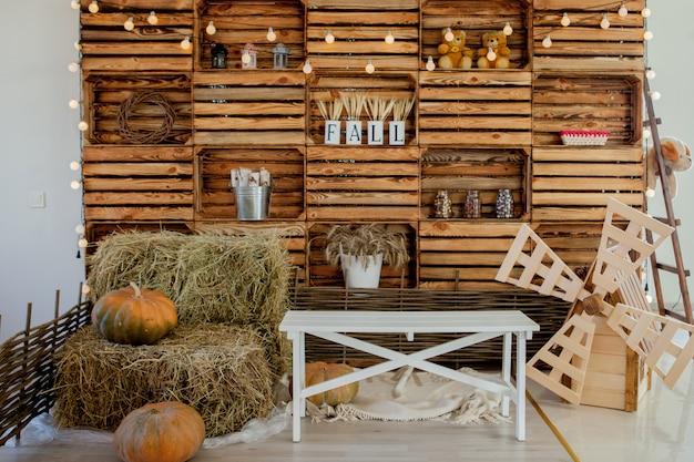 Drewniana ściana ozdobiona lampami elektrycznymi i znakiem miłości. vintage walizki i poduszki na podłodze.