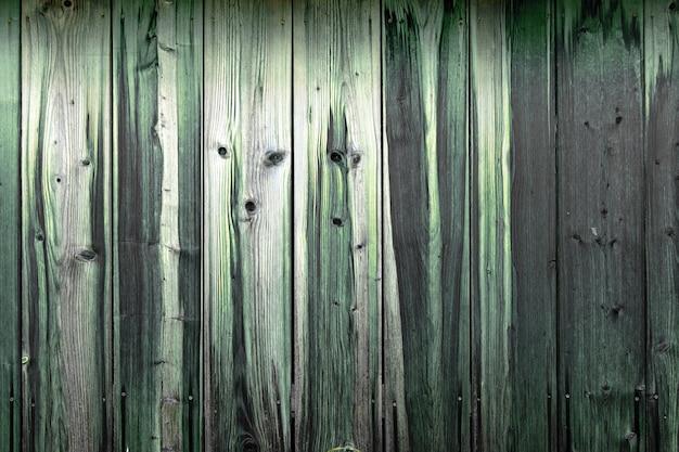 Drewniana ściana szarych desek z wizerunkiem pyska zwierzęcia.