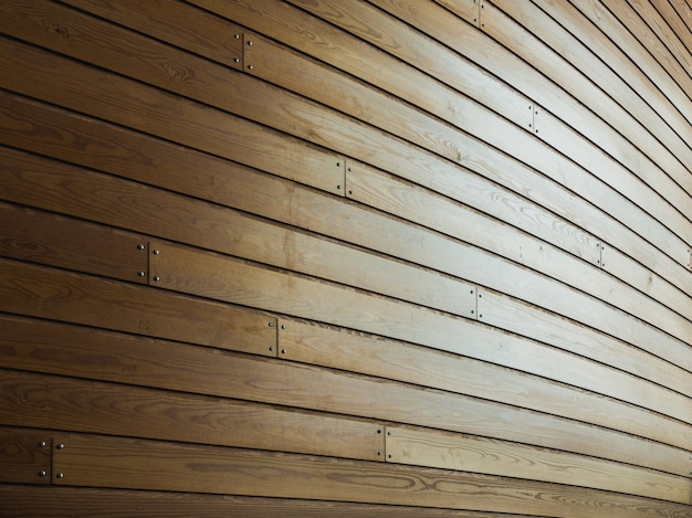 Drewniana ściana z gwoździami w nim w świetle słonecznym