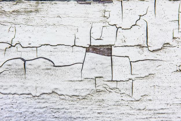 Drewniana ściana z krakingową starą białą farbą