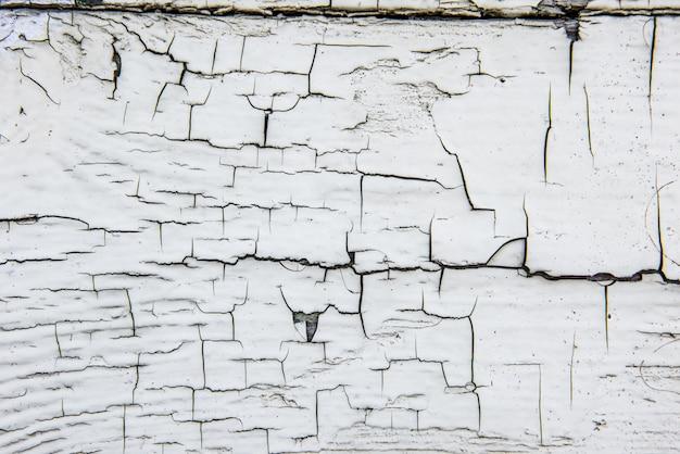 Drewniana ściana z popękaną starą białą farbą