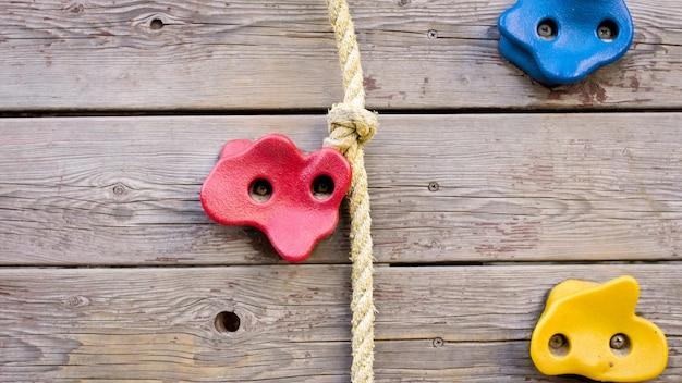 Drewniana ścianka do wspinaczki z plastikowymi uchwytami i linami na placu zabaw.