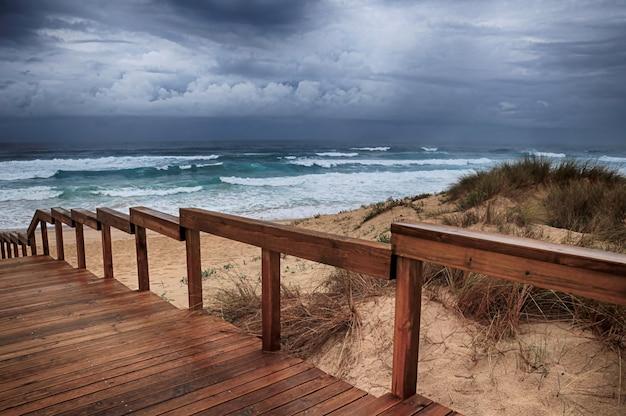 Drewniana ścieżka na plaży przy zapierających dech w piersiach falach oceanu pod zachmurzonym niebem