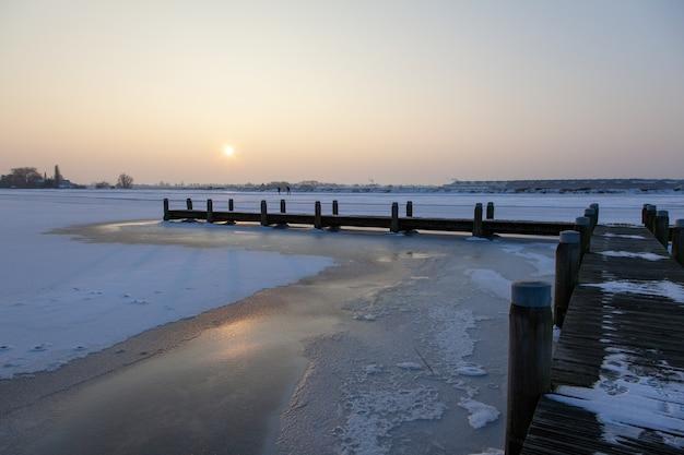 Drewniana ścieżka nad zamarzniętą wodą z zamglonym niebem
