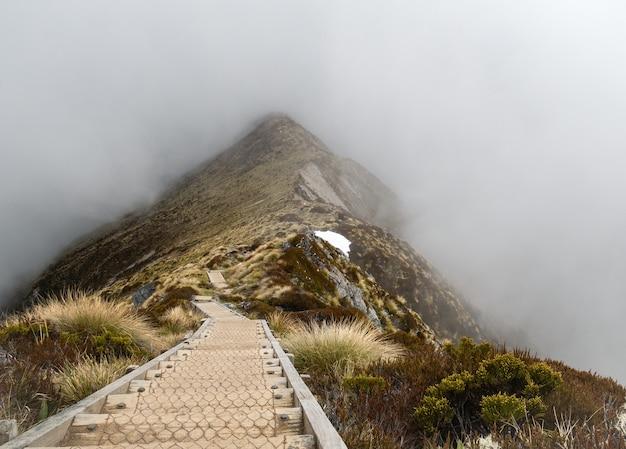Drewniana ścieżka prowadząca przez górski grzbiet osnuty mgłą kepler track nowa zelandia
