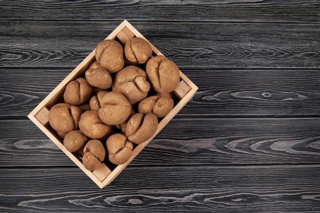Drewniana skrzynia pełna świeżych surowych brzydkich ziemniaków. widok z góry.