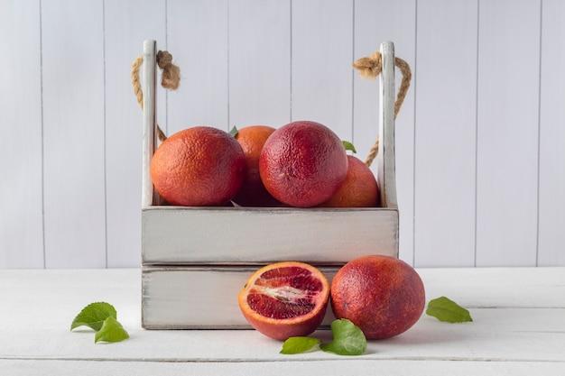 Drewniana skrzynia z krwią pomarańczy na białym stole. ekologiczne owoce cytrusowe