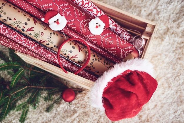 Drewniana skrzynia z papierem świątecznym i czapką mikołaja