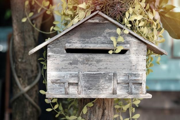 Drewniana skrzynka pocztowa w kwiatu ogródzie, rocznika brzmienie