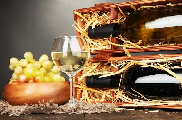 Drewniana skrzynka z butelkami wina, kieliszkiem i winogronem na drewnianym stole na szaro