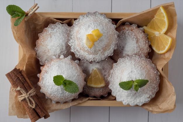 Drewniana skrzynka z smakowitymi cytryn muffins na bielu stole, odgórny widok