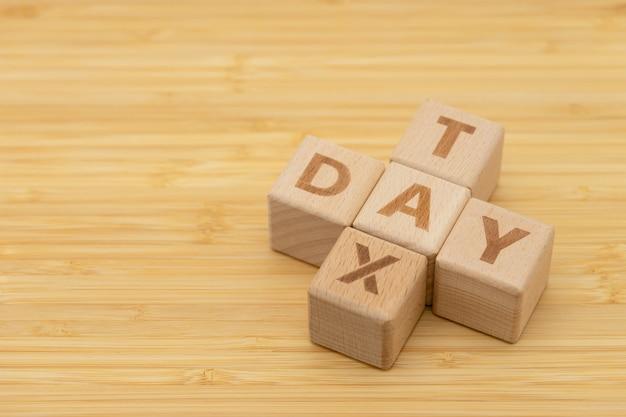 Drewniana słowo podatku dnia pozycja na drewno stole używać jako tło biznesu pojęcie