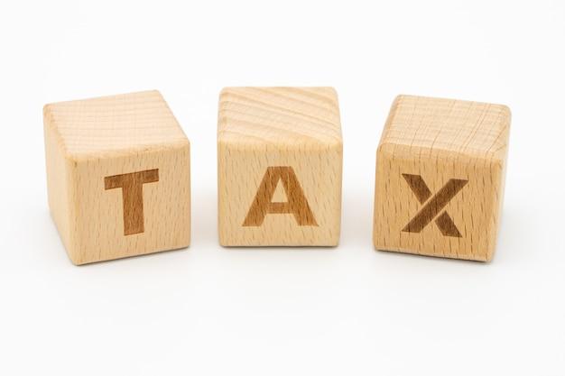 Drewniana słowo podatku pozycja na białym tle odizolowywa
