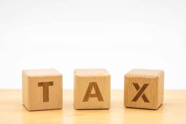 Drewniana słowo podatku pozycja na drewno stole używać jako tło biznesu pojęcie