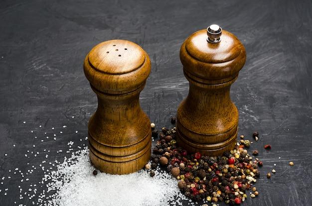 Drewniana solniczka i pieprzniczka. przyprawia sól i pieprzy na czarnej kredowej desce
