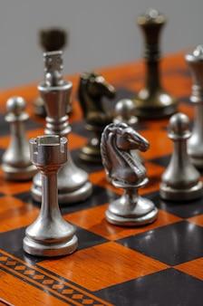 Drewniana szachownica z kawałkami metalu. szach mat.