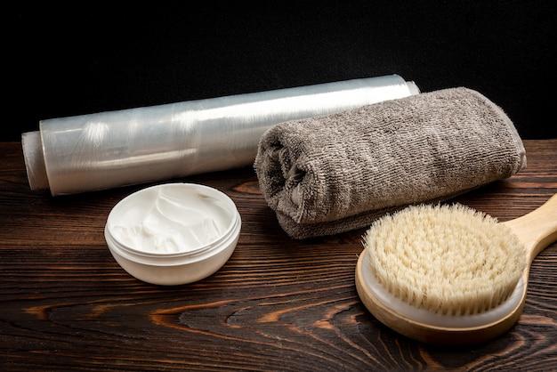 Drewniana szczotka do masażu, krem i ręcznik na ciemnym drewnianym stole.