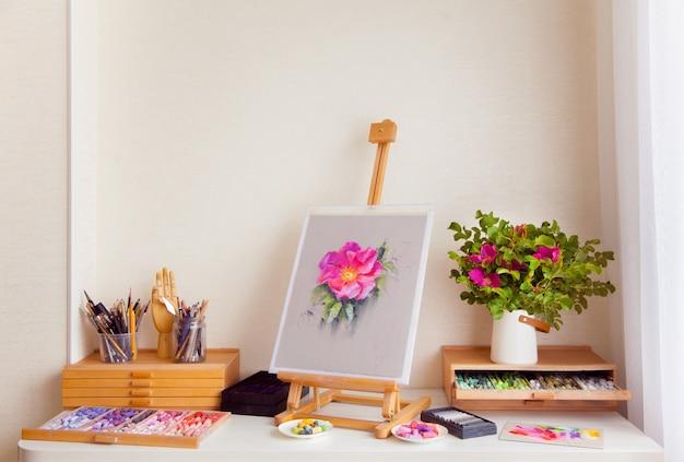 Drewniana sztaluga szkicu różowego kwiatu dzikiej róży stoi na stole obok materiałów do rysowania pędzlami, ołówkami i suchym pastelem. koncepcja miejsca pracy artystki. copyspace