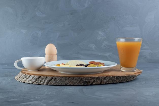 Drewniana tablica i papierowa okładka pod zestawem dań śniadaniowych na marmurowym stole.
