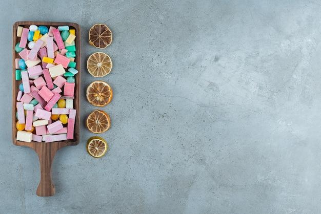 Drewniana tablica kolorowych gum balonowych i plasterków cytryny na kamieniu.
