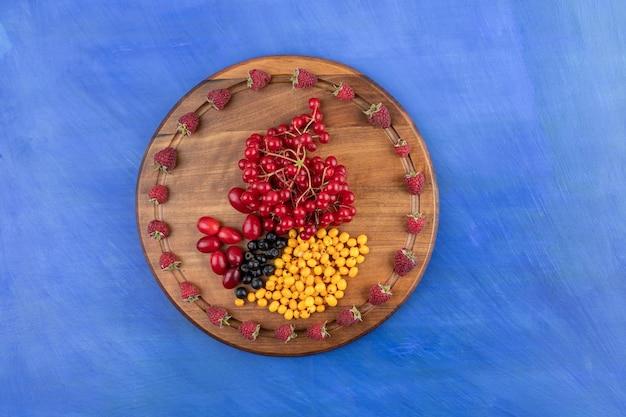 Drewniana tablica pełna jagód na niebieskiej powierzchni