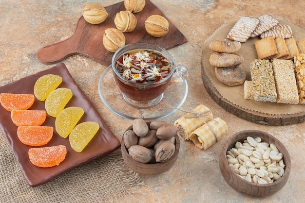 Drewniana tablica pełna słodkich ciasteczek i filiżanki herbaty ziołowej