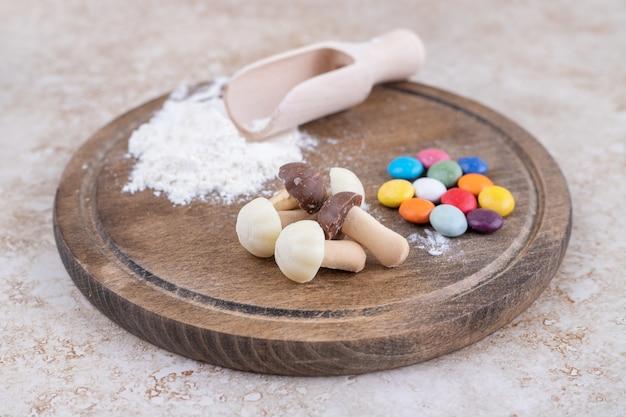 Drewniana tablica pełna słodkich grzybów z kolorowymi cukierkami
