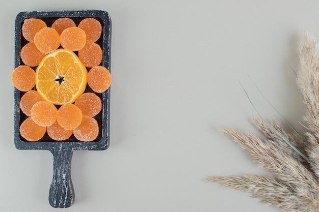 Drewniana tablica pełna słodkich żelków i plasterek pomarańczy.