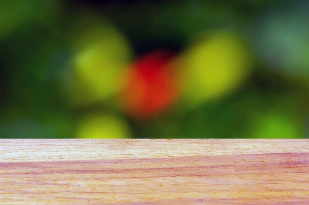 Drewniana tablica pusty stół przed zielonym czerwonym tłem bokeh do wyświetlania produktu