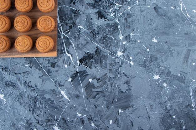 Drewniana tablica słodkich okrągłych ciasteczek z filiżanką smacznej gorącej kawy na marmurowym tle.