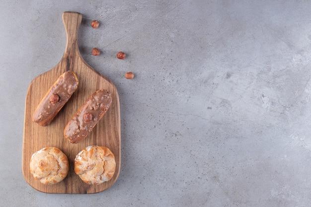 Drewniana tablica słodkich profiteroles i eklerów na kamiennej powierzchni
