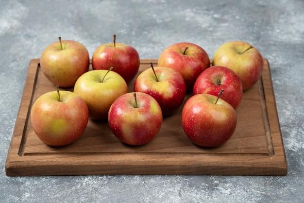 Drewniana tablica świeżych, pysznych jabłek na marmurowej powierzchni.