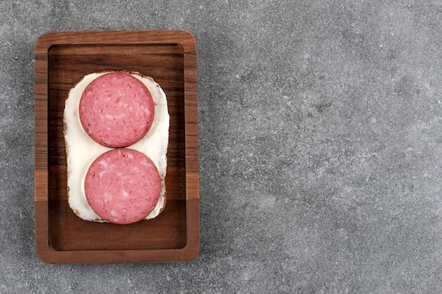 Drewniana tablica tostów z salami umieszczona na kamieniu.