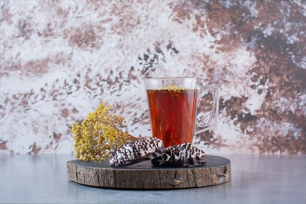 Drewniana tablica z filiżanką gorącej herbaty z ciasteczkami i kwiatem mimozy