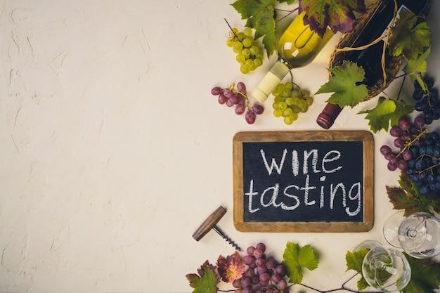 """Drewniana tablica z napisem """"degustacja wina"""", butelka wina, winogron i liści winogron."""