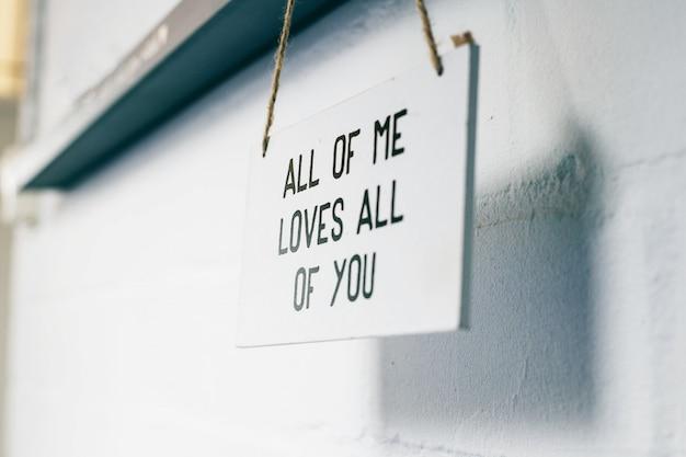 Drewniana tablica z tekstem wszyscy kocham was wszystkich, znak miłości na ścianie domu wnętrze nowoczesne
