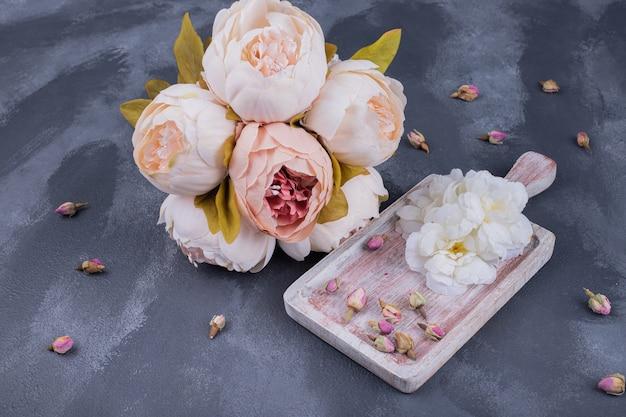 Drewniana tablica z uschniętą różą w ciemności.