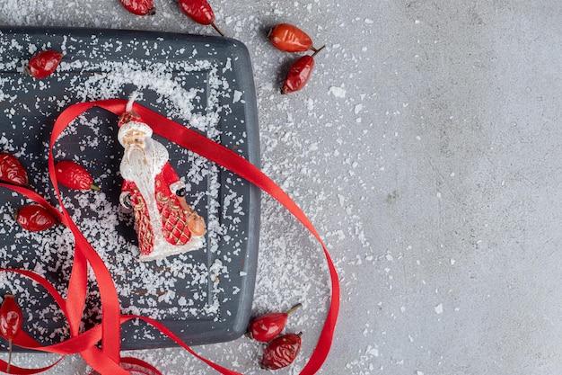 Drewniana taca. biodra, czerwone wstążki, nożyczki, proszek kokosowy i figurka mikołaja na marmurowym stole.