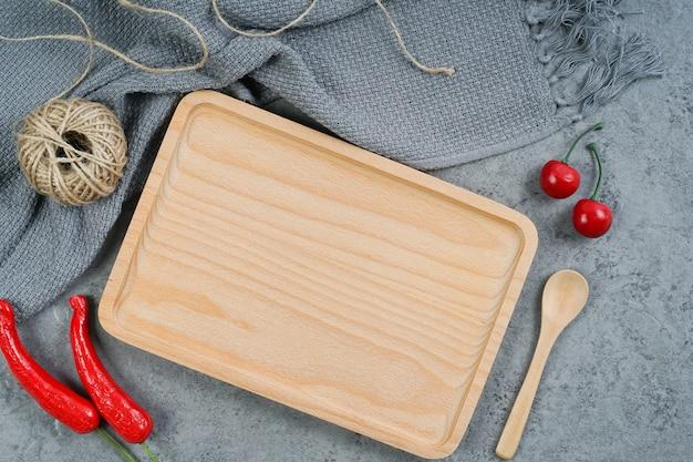 Drewniana taca, czerwone chili, drewniana łyżka, czereśnie i nić