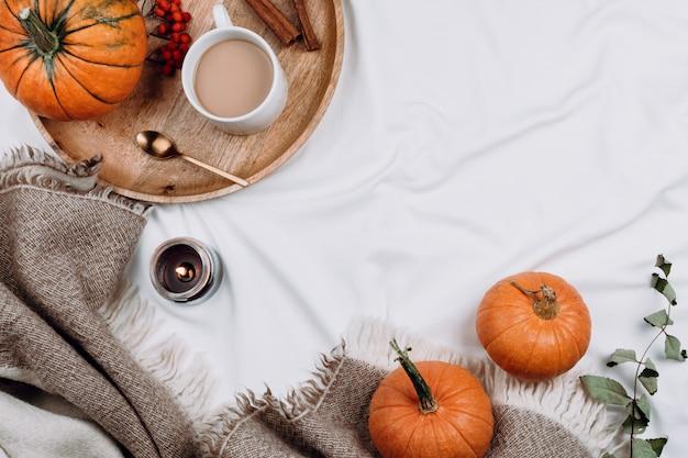 Drewniana taca, filiżanka kawy lub kakao, świeca, dynie na białych prześcieradłach i kocach