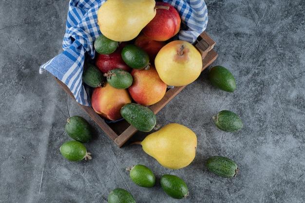 Drewniana taca na owoce pełna gruszek, feijoa i brzoskwiń