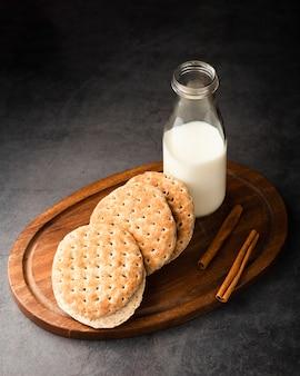 Drewniana taca pod wysokim kątem z mlekiem i ciastkami