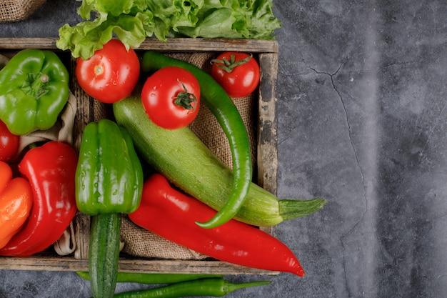 Drewniana taca z czerwonych i zielonych warzyw.