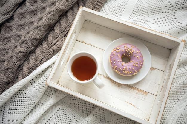 Drewniana taca z herbatą i serwowanym pączkiem
