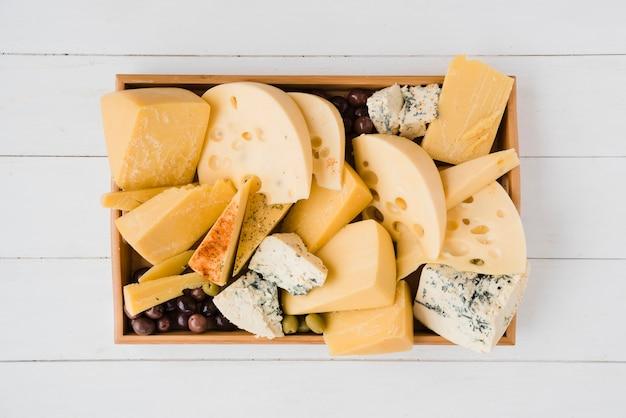 Drewniana taca z kilkoma plasterkami średnio twardego szwajcarskiego sera z oliwkami zielonymi