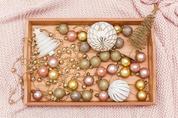 Drewniana taca z ozdób choinkowych na ciepłej różowej kratce z dzianiny. koncepcja świąt lub nowego roku.