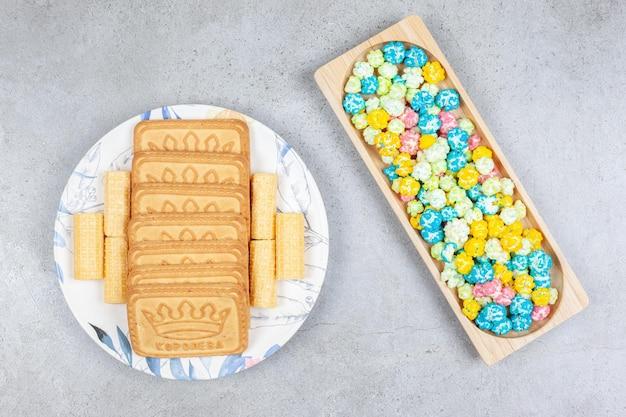 Drewniana taca z popcornowymi cukierkami z herbatnikami na talerzu na marmurowym tle. wysokiej jakości zdjęcie