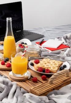Drewniana taca ze szklanką soku pomarańczowego i kanapką z jagodami na łóżku