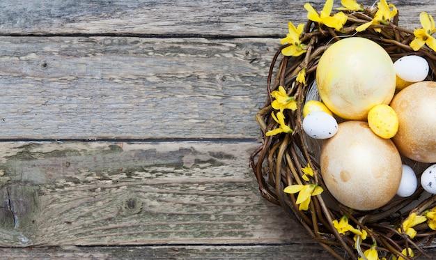 Drewniana tekstura z złotymi i żółtymi jajkami w gniazdeczku z kwiatami. skopiuj miejsce na tekst wielkanocny