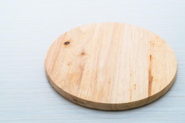 Drewniana tnąca deska na drewnianym tekstury tle